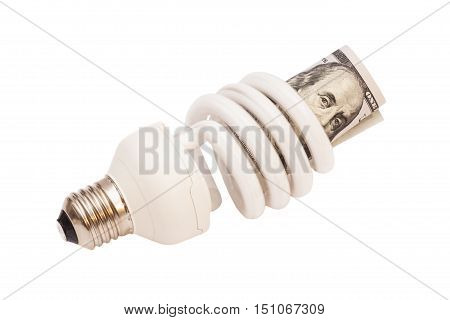 Energy saver bulb with 100 dollar bills on white background
