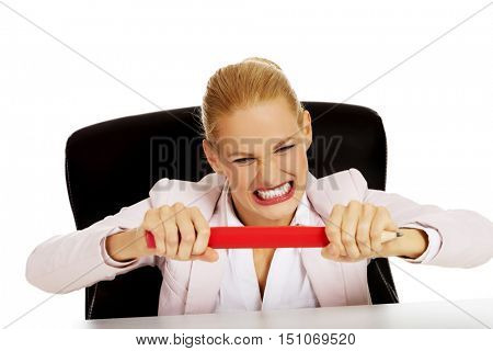 Angry business woman sitting behind the desk and trying to break huge pen