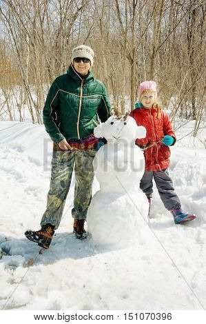 Mother And Daughter Next To A Snowman