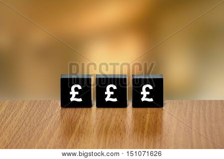 british pound currency on black block with blurred background