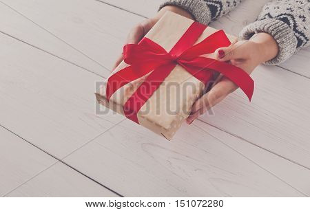 Woman's hands give wrapped christmas or other holiday handmade present in paper with red ribbon. Present box, decoration of gift on white wooden table with copy space