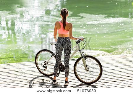 beautiful elegance brown hair back woman happy fun blue sky pink t-shirt sport wear bicycle urban city portrait nature slim sport body hobby equipment riding bike cyclist