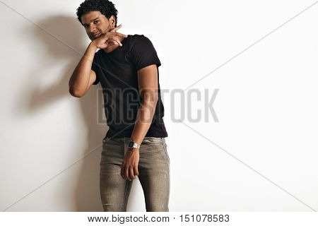 Dancing smiling relaxed black young model in an unlabeled black t-shirt and skinny grey jeans isolated on white