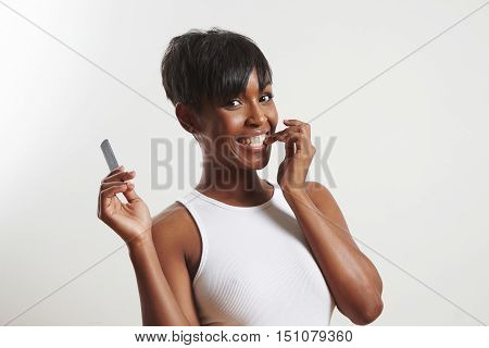 Woman With A File In One Hand Bites A Nail On Another
