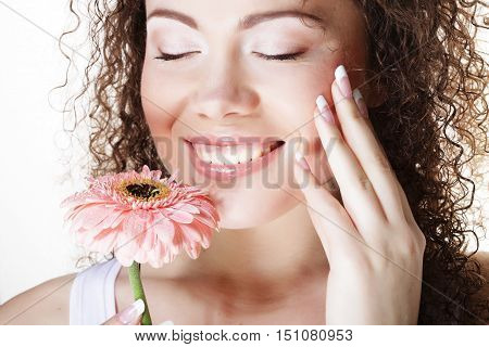 People, health and spa concept: beautiful young woman with big pink gerber