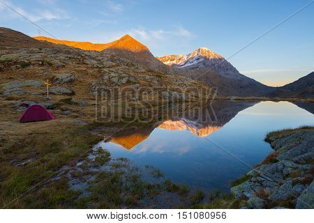 Camping With Tent Near High Altitude Lake On The Alps. Reflection Of Snowcapped Mountain Range And S