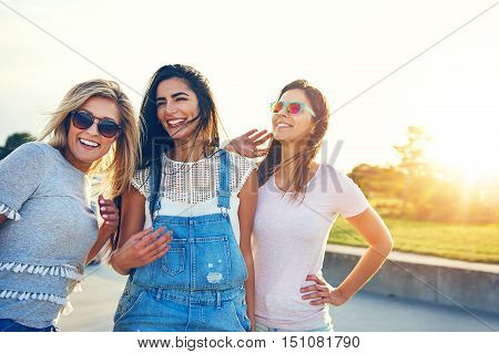 Three multiracial women friends at the seaside standing arm in arm on a beachfront promenade in the rising summer sun laughing and smiling