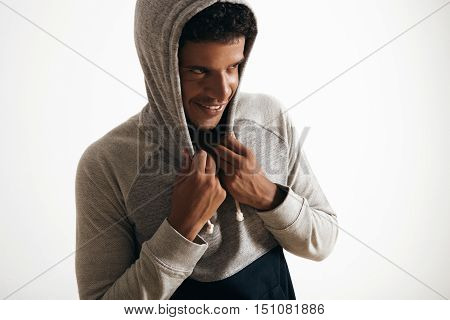 Attractive black man wears hoodie on his head with curly hair , looking miraculously on side and happily smiling, isolated on white