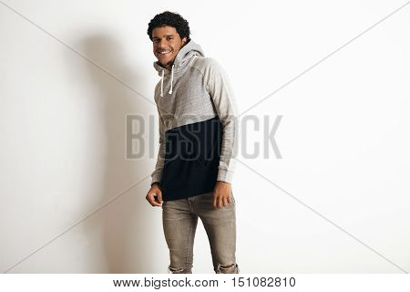 Happy smiling attractive latino guy wears blank grey black sweater with hood and distressed jeans, isolated on white