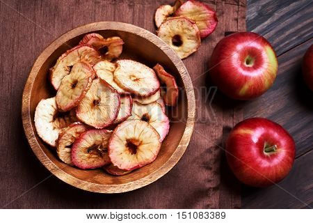 Dehydrated apples chips in wooden bowl top view