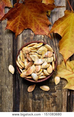 Pumpkin seeds and colorful autumn leaves on wooden background top view