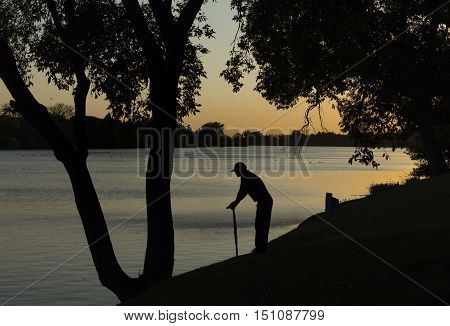 horizontal silhouette of an old man leaning on walking cane looking out across the lake at sunset with trees lining the banks on a summer evening.