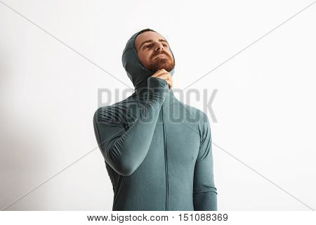 Attractive young bearded athlete lock zip while wearing hood of his wither snowboard baselayer thermal suite