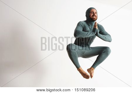 Happy smiling bearded young athlete wearing thermal baselayer suite and jumping like a ninja in air, isolated on white