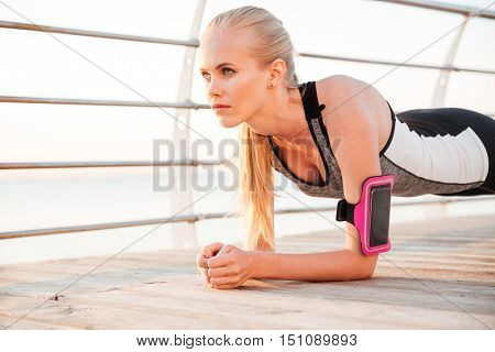 Fitness woman doing planking yoga exercises outdoors at the beach pier