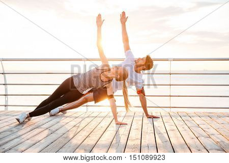 Smiling couple doing yoga exercises outdoors at the beach pier