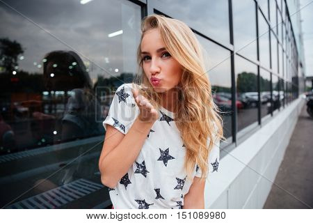Beautiful young woman sending air kiss while standing outdoors