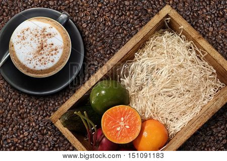 Fruit box and cappuccino coffee over brick wall background