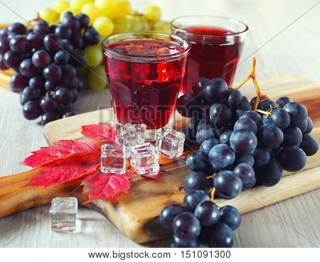 Two glasses of grape juice with ice and black and green grapes. Toned image