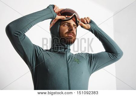 Young fitted bearded male athlete in baselayer thermal suite with hands on his snowboarding googles, looking on side, isolated on white