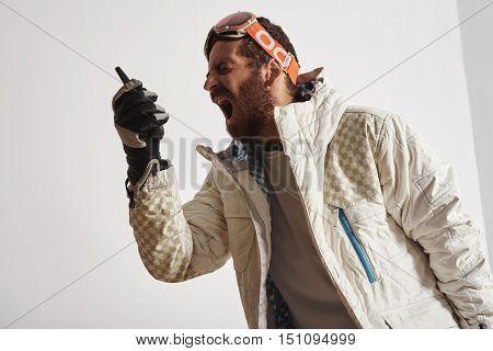 Man in snowboard gear with googles on head screaming into walkie talkie