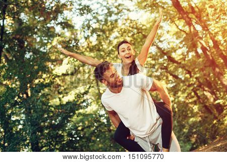 Young happy couple piggyback fun in the park
