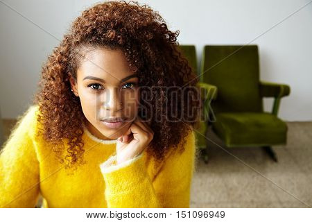 Portrait of thoughtful young beautiful black girl with curly hair looking on camera, closeup
