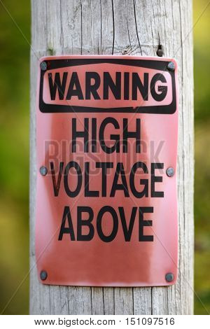 Warning High Voltage above sign on an electric line post.