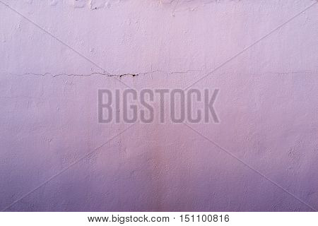 the abstract textured background of an old surface of the plastered wall of a motley lilac color tonality