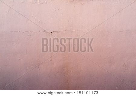 the abstract textured background of an old surface of the plastered wall of a motley pink color tonality