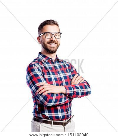Young handsome hipster man in checked red and blue shirt, arms crossed. Studio shot on white background, isolated.