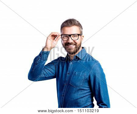 Young handsome hipster man in blue denim shirt, holding his black eyeglasses. Studio shot on white background, isolated.
