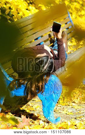Attractive young woman laying on a brown wooden bench with mobile phone in her hands in a beautiful park. She looks to the cell phone. Golden autumn foliage around. Girl wears blue jeans and turtleneck sweater. Yellow color dominates