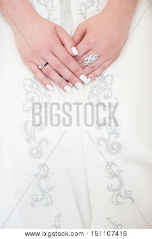 hands of young woman with rings lying on the patterned dress