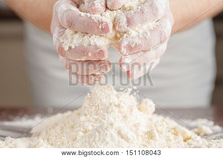 Hands kneading a dough on wooden table