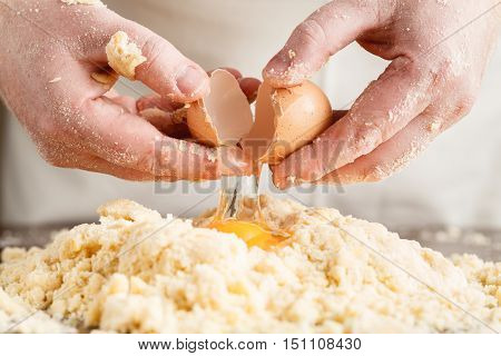 person hands kneading dough on wooden table