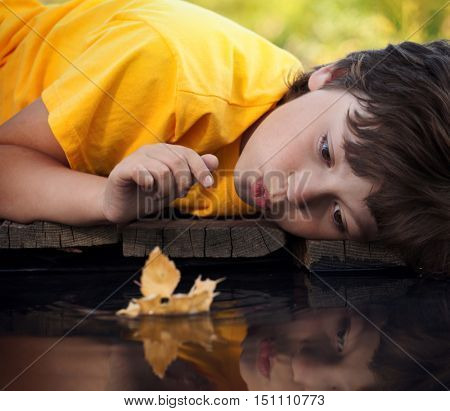 boy play with autumn leaf ship in water (focus on ship)