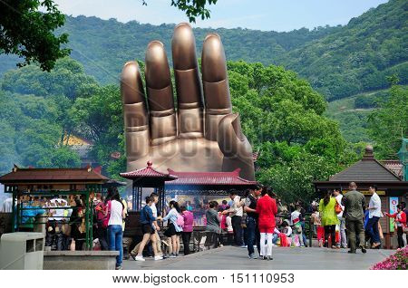 May 17 2015. Wuxi China. Chinese tourists walking around Buddha's hand at the Lingshan Buddhist scenic area in Wuxi China in Jiangsu province.
