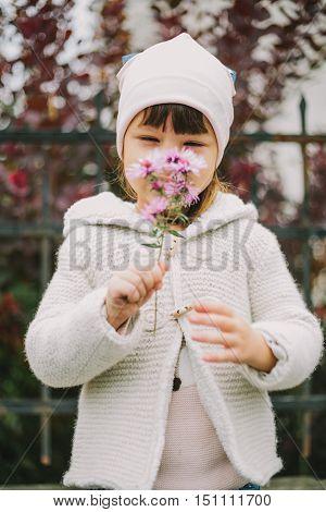 girl sniffs a flower . purple background.