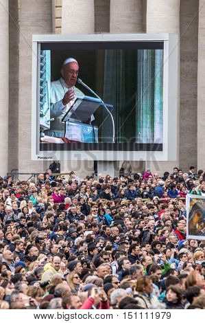 Rome 23 March 2014: A group of believers in St. Peter's Square careful listening to the Angelus of the Pope Francis. Pope Francis on the big screen. March 23 2014 Vatican City Italy