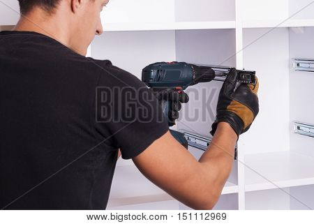 furniture maker sets telescopic rails on the cabinet