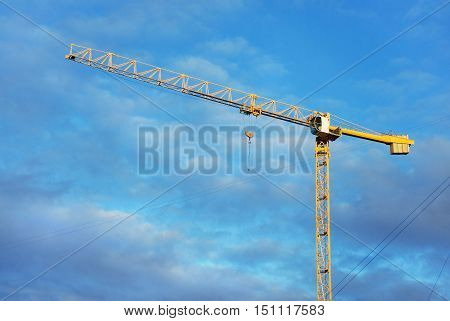 Building tower crane on a background of blue sky and clouds