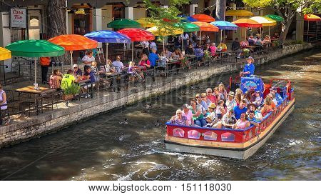 SAN ANTONIO, TEXAS - APRIL 14: A tour boat passes a restaurant along the historic San Antonio River Walk in downtown San Antonio, Texas on April 14th, 2016.