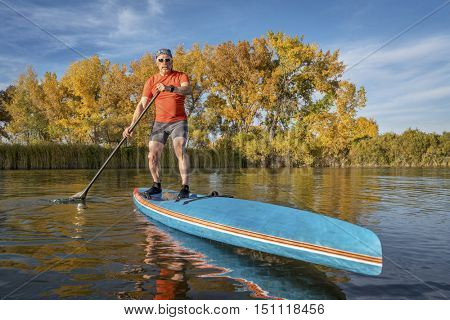 Senior male paddler enjoys workout on his racing stand up paddleboard in fall colors on a lake in Colorado
