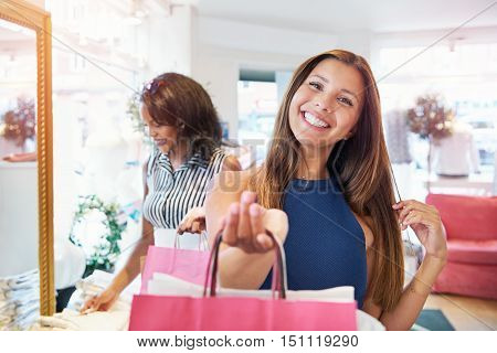 Vivacious young woman shopper grinning at the camera as she stands in a clothing boutique proudly holding up her purchases in pink bags