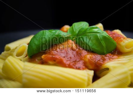 Close up of pasta dish with fresh tomato sauce. Rigatoni with red Sauce and basil leaves. Italian Noodles. Homemade Noodles with.