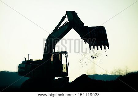 Silhouette excavator on construction site, construction site