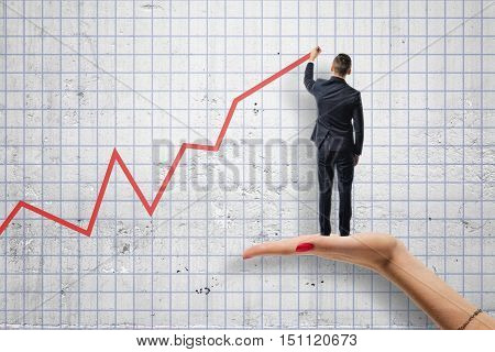 Back view of businessman drawing a red diagram standing on woman's hand. Help and support from investors. Setting and achieving goals. Increase in income. Support of small business.