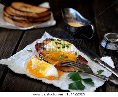 Poached with bacon and toast, parsley on paper, fork and knife on dark wooden background