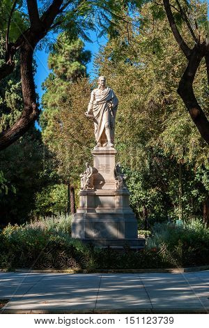 Monument with three sculptures among the green trees of the national Park of Athens.